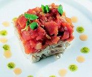 Met basilicum en olie gegaarde kabeljauw met een tomatenfondue