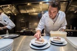 Hans van Wolde achter kachel Glazen Restaurant